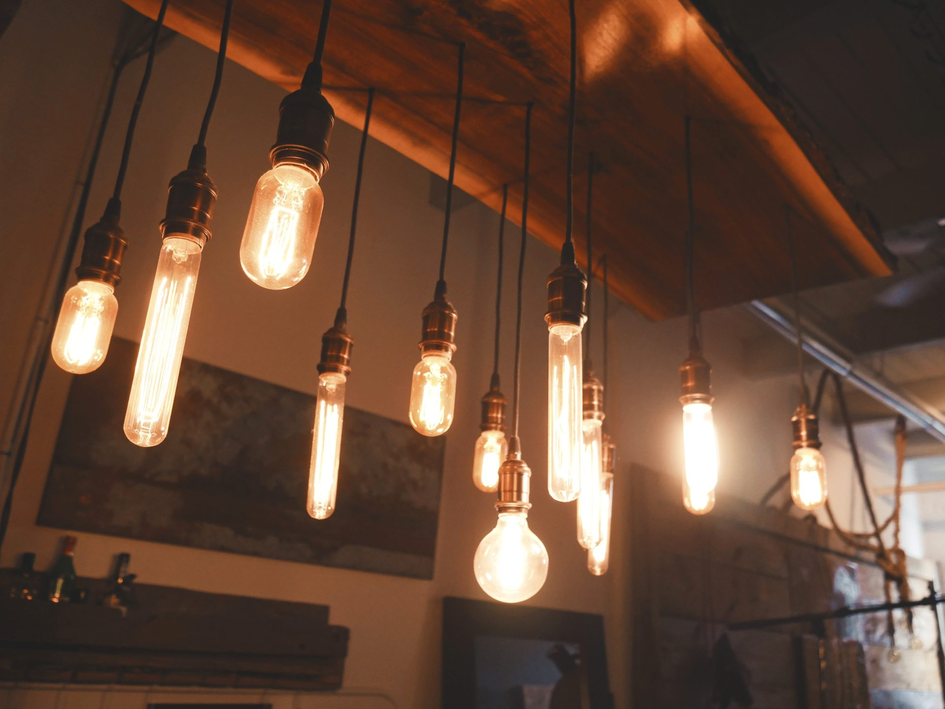 A variety of glowing Edison-style lightbulbs hang from the ceiling (Photo by Patrick Tomasso on Unsplash)