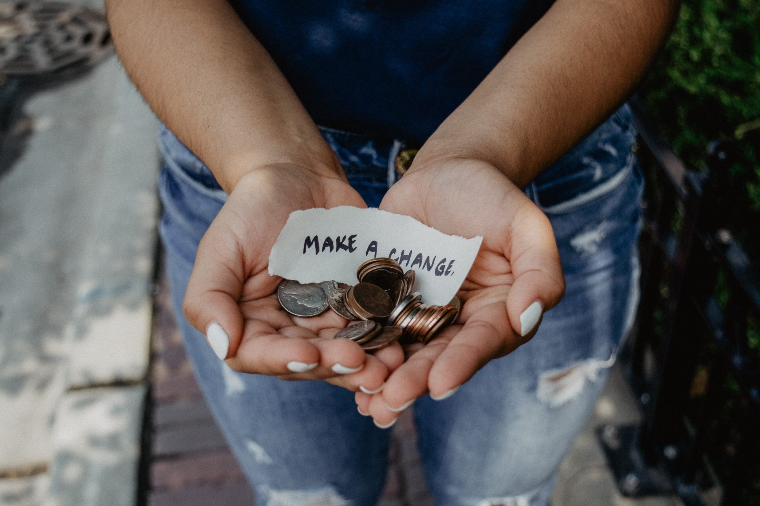 "A woman holds spare change in her cupped hands with a note saying ""Make a change"" (Photo by Kat Yukawa on Unsplash)"